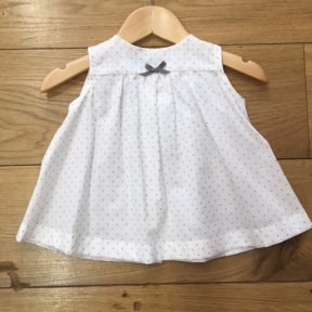 White cotton dress with full length shell buttons to the back. Printed grey polka-dots and a little grey bow at the front.