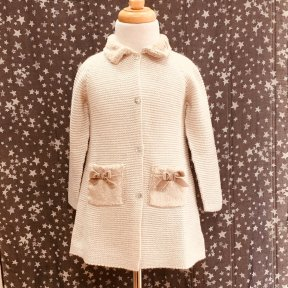 Floc girls long beige knitted jacket, embellished with a soft faux-fur collar and 2 pocket detail with gold velvet bows. Full length mother-of-pearl fastening to the front.