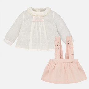 Mayoral baby girls 2 piece set.The Ivory blouse is long sleeved with smocking and a ruffled round neck collar. There are buttons to the  back. The pink skirt has straps  with embroidered flower detail and hidden buttons. There is an adjustable elasticated