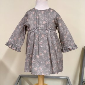 Wedoble girls grey and peach cotton winter dress. Fully lined, long sleeved with pleat and bow details to the yoke and frill cuffs. Half length zip fastening to the back.