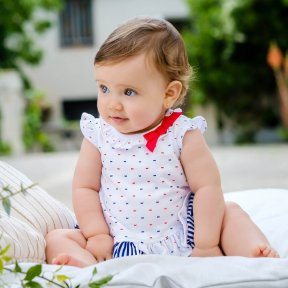 Red, white and navy blue dress set by Tutto Piccolo, soft cotton jersey. The white dress is printed with tiny blue and red bows, has a red bow detail to the neck line & embroidered logo, It also has a striped ruffle around the hem. The matching navy blue
